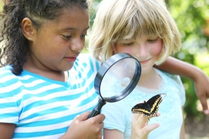 Two girls looking closely at a butterfly.