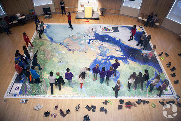 Children walk across a giant floor map of the Arctic.