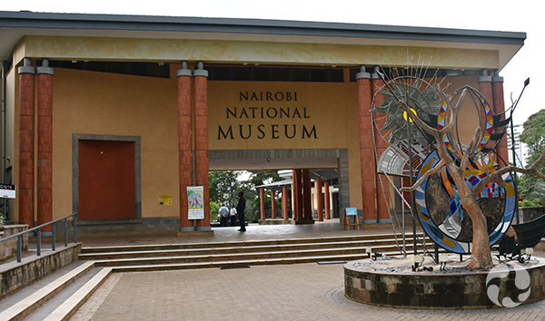 Entrance of the Nairobi National Museum, which includes a courtyard with sculpture in front.