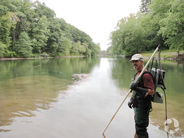 A man standing in a creek holding electrofishing gear.