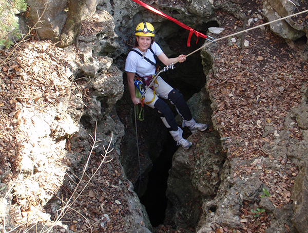 A woman hangs in front of a cave opening.
