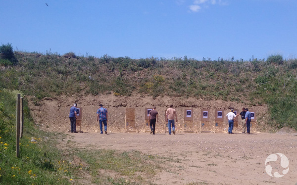 Men approach their targets, which stand in front of a hill.