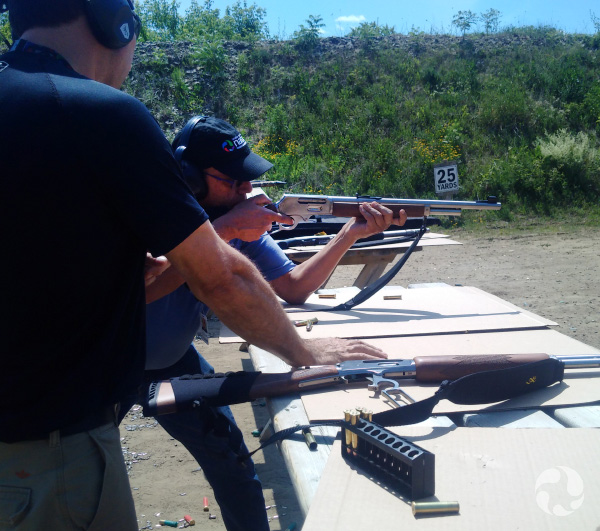 A man aims a rifle while another looks on.