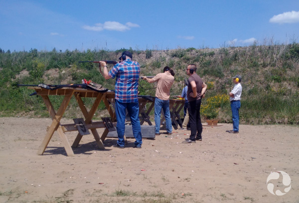 Men standing at tables take aim while others observe.