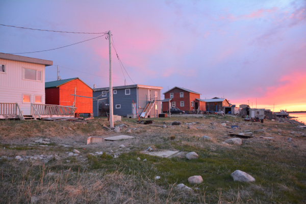 Arviat houses in the foreground, with a sunset in the background.