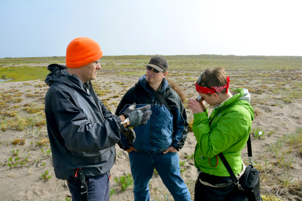Three people in a semi-circle stand on the tundra.