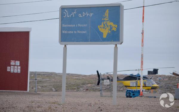 "A sign that says ""Welcome to Naujaat"" in English, French and Inuktitut, with a helicopter and building in the background."