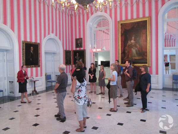 A dozen people stand inside a grand room.