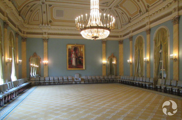 Chairs circle the walls in a very large room.