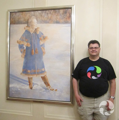 A man stands beside a painting on a wall.