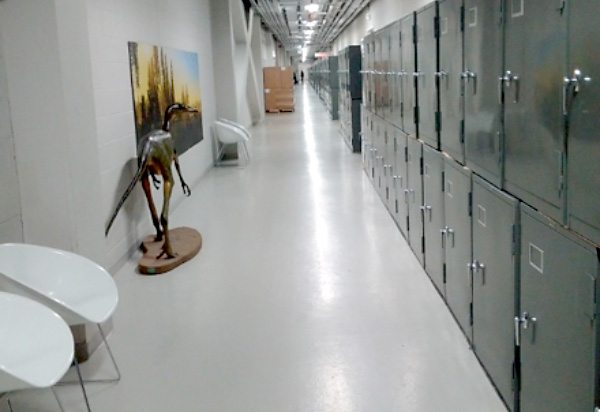 A very long corridor with a double stack of single-door cabinets along one side.