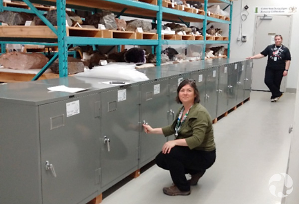 Two women pose with a row of single-door cabinets.
