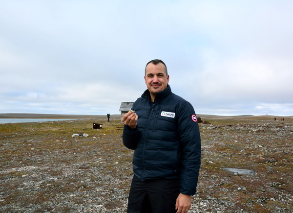 A man standing on the tundra in Nunavut holding a lichen.