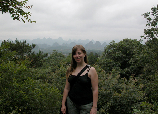 A woman standing in front of bushes in Guangxi, China.