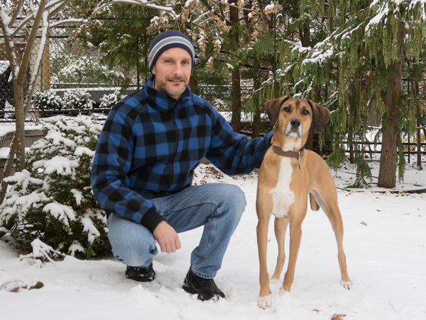 A man wearing a blue-and-black checkered jacket, crouched down in the snow with his dog