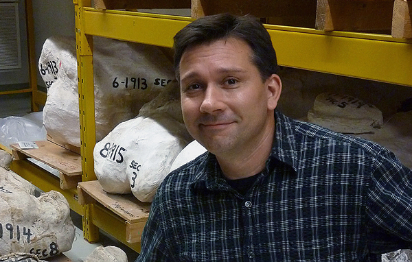 A man poses before plaster jackets containing dinosaur fossils.