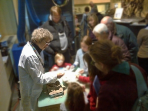A woman standing over fossils on a table talking with museum visitors.