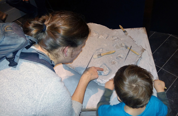 A woman and a boy examine dinosaur fossils at a museum activity station.
