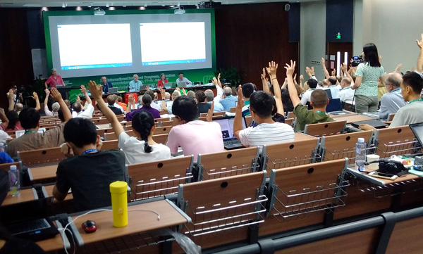 Four people are presenting to a full auditorium. Conference attendees in the auditorium are voting on questions posed during the presentation by raising their hands.