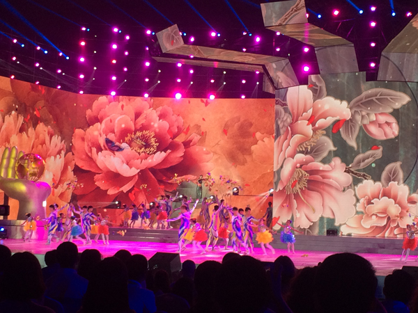 Performers dance on a stage in front of large images of plants.
