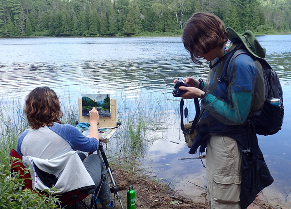 A woman paints near the river, another woman examines photographs on her camera
