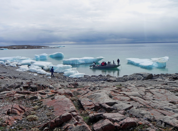 People arriving by boat on an Arctic shoreline.