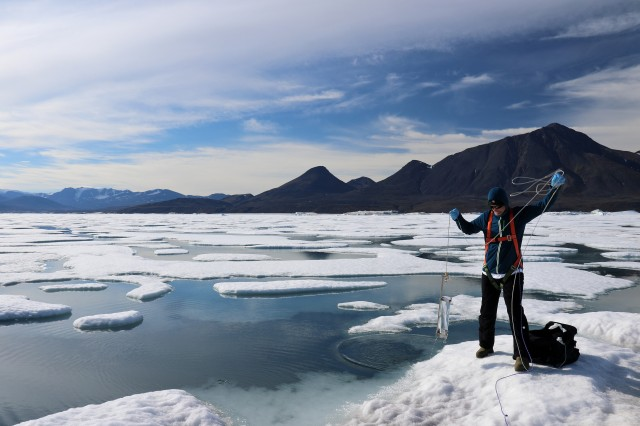 In the image is a man standing on ice in front of a partially frozen water body. He is collecting a water sample with a cylindrical container with a very long rope attached. In the background there are mountains.