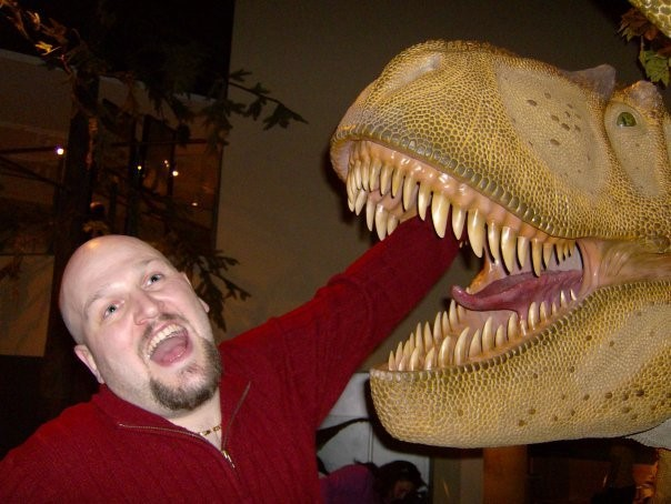 bald man with arm put inside a dinosaur models mouth