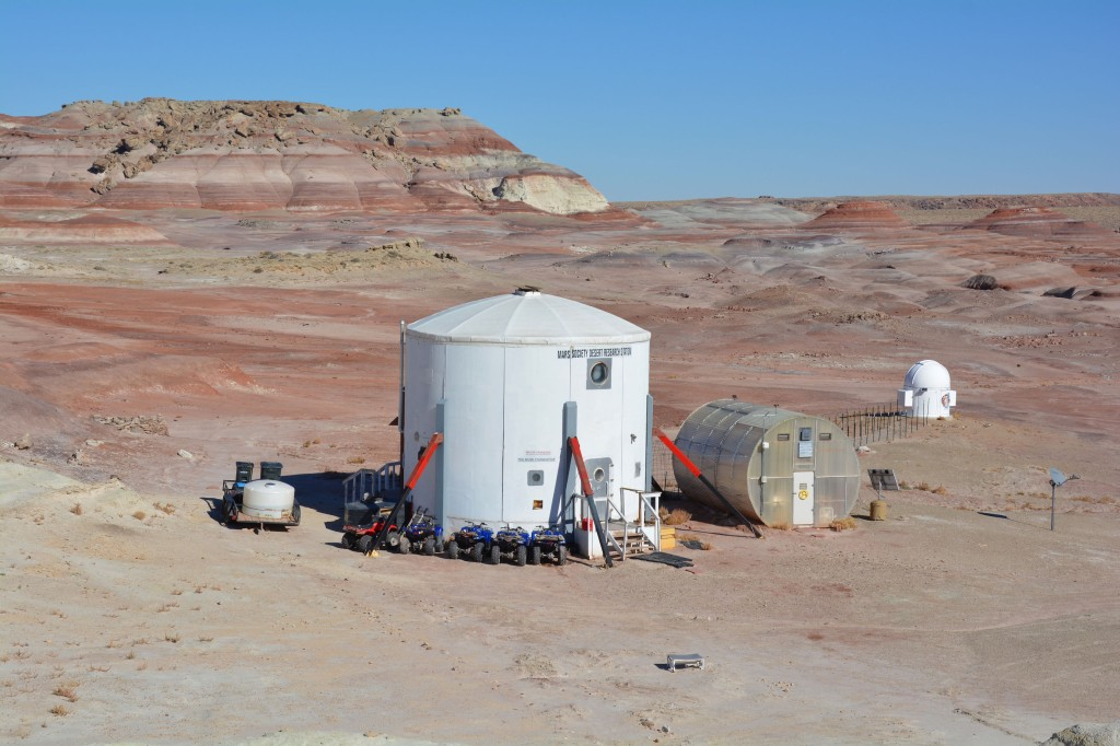 A white simulated mars habitat in the foreground, set in an empty red desert.