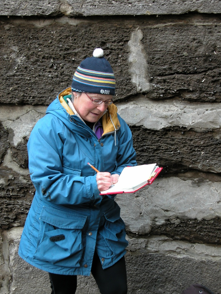 A woman in outdoor winter clothing, standing in front of a brick wall, writing in a red notebook.