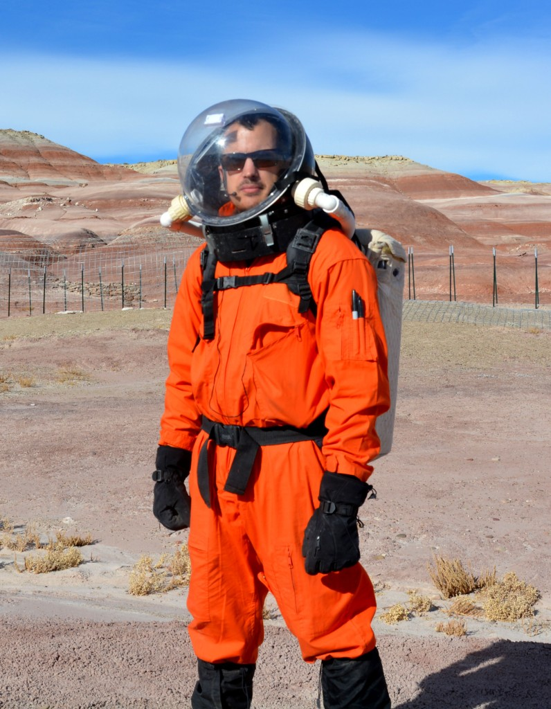 A man wearing a simulated spacesuit in a desert.