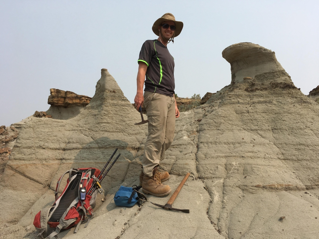 Photograph of a man walking in the Alberta Badlands.