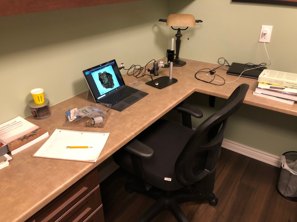 Photograph of desk with computer and microscope.