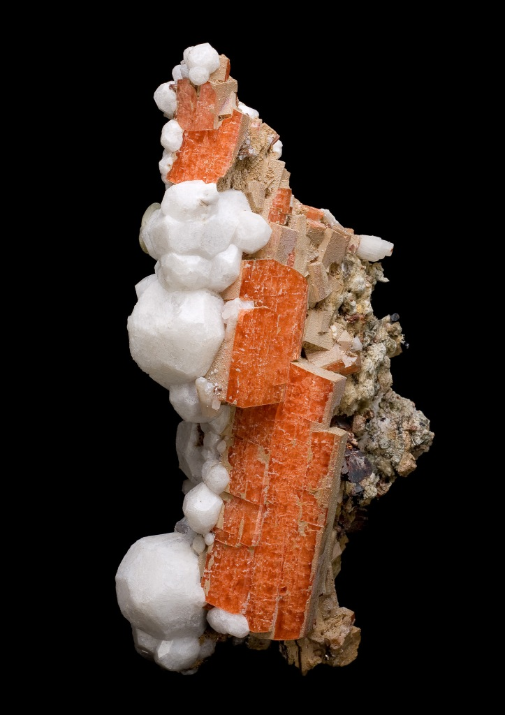 Vertically oriented orange sample of serandite with white crystals of analcime.
