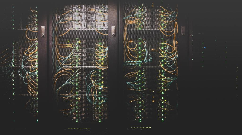 Image of a computer server's electronic components. There are lots of coloured wires and green lights inside a metallic cage.