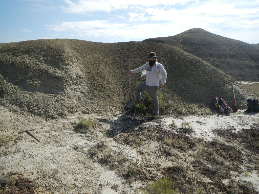 Man standing in front of a small dirt hill holding a shovel.