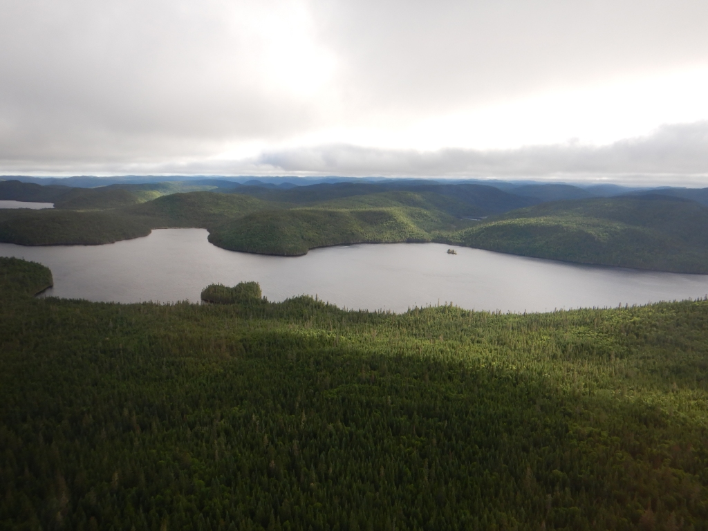 Photo of a large lake surrounded on all sides by thick forest. There are clouds in the sky, but you can still see sunlight hitting the forested hills.
