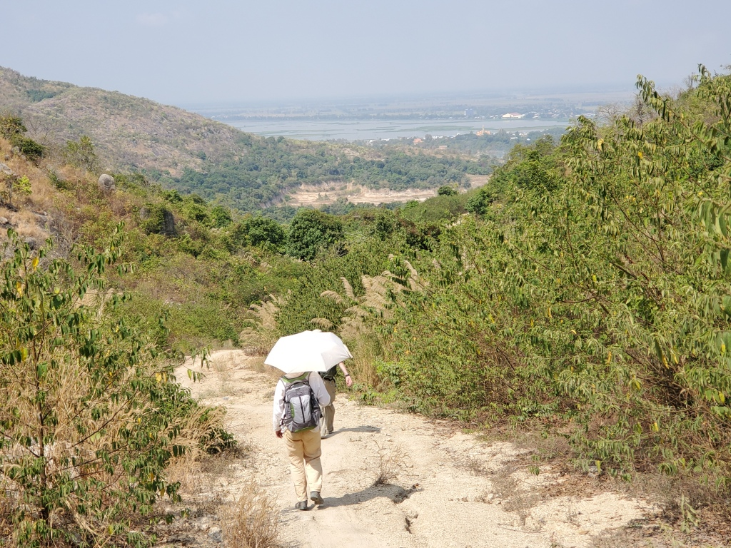 Museum scientists hiking down a dusty trail on Phnom Bayong in Takeo province, Cambodia.