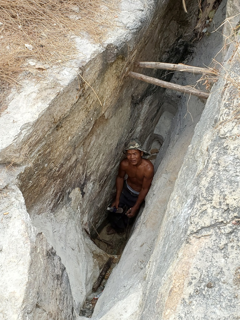 A miner works in a trench to extract fluorite from a vein.
