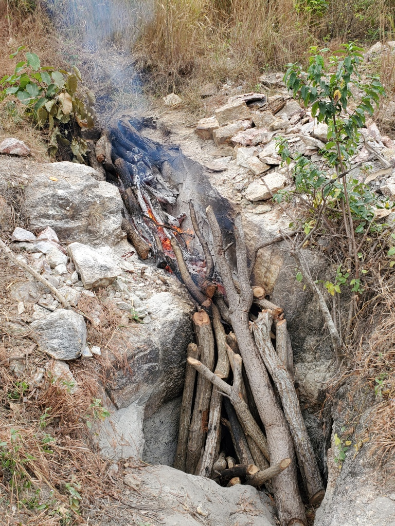 Logs in a trench are set on fire to expand the rock.
