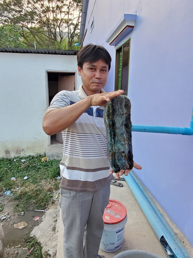 Mr. Sokphun holds up a large piece of green and purple fluorite from his mine.