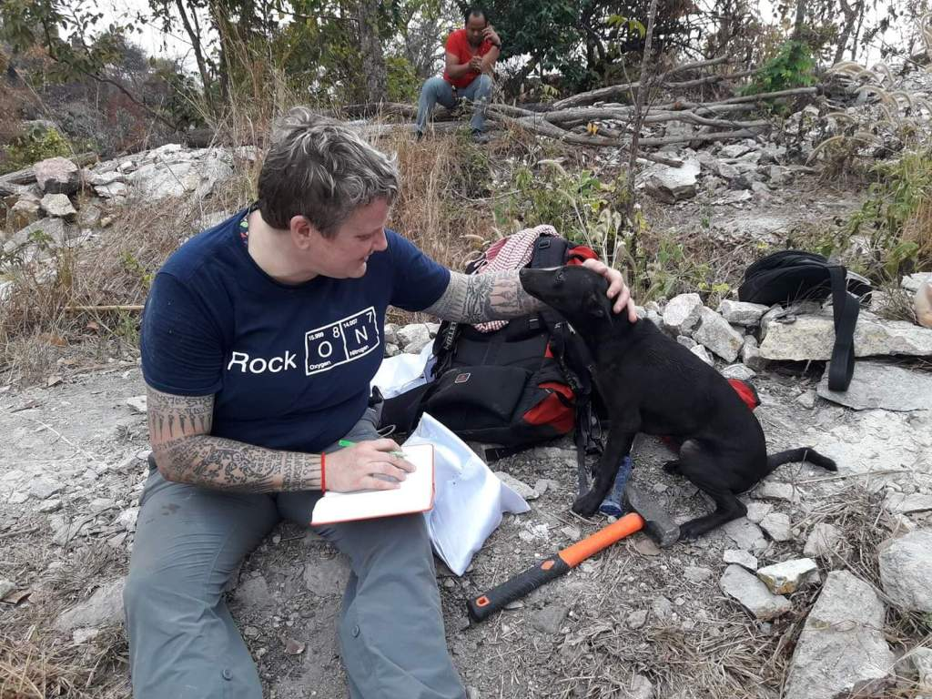 Mineralogist Paula Piilonen meeting some of the local dogs while examining mineral samples.